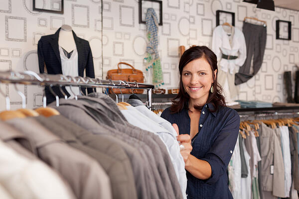 Portrait of happy female customer choosing shirt in clothing store